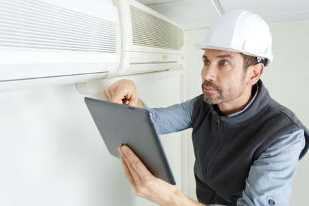 air conditioning technician looking at tablet Banque d'images