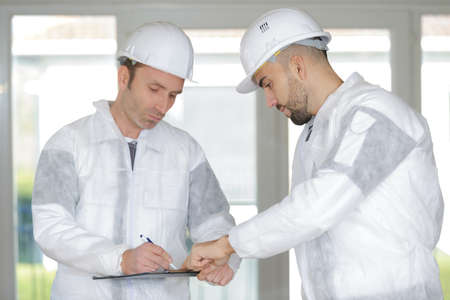 Workers in protective overalls writing on clipboard
