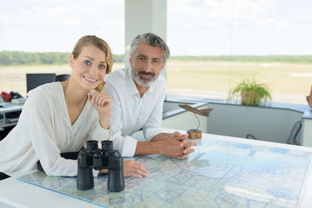 man and woman in traffic control tower at an airport