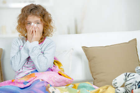 Young girl sat on couch, blowing nose