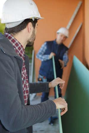 workmen preparing to move large board
