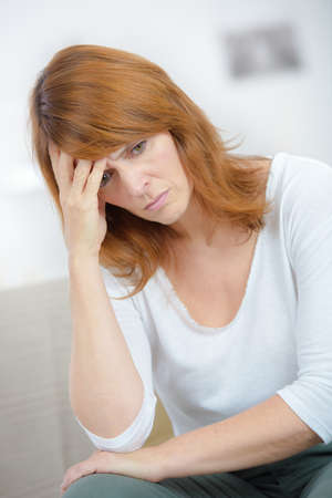 middle aged woman with a worried expression holding her head