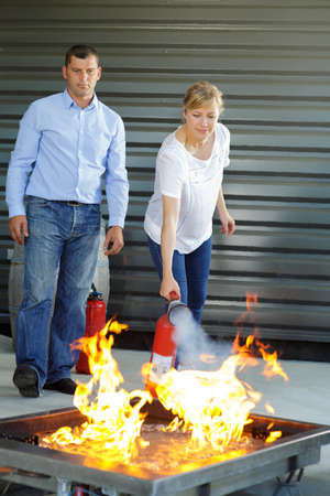 closeup woman operating a fire extinguisher