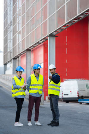workers in high-visibility vests by loading bays Stock Photo