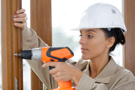 female builder using a cordless screwdriver