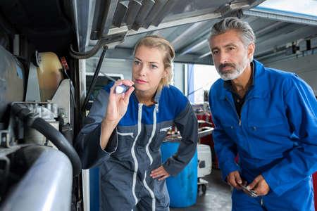 männliches und weibliches Mechanikerteam untersuchen einen Motor Standard-Bild