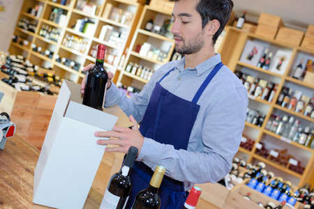 glad young man seller wearing uniform in wine house