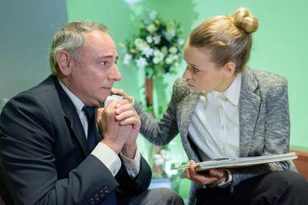female funeral director consoling senior man