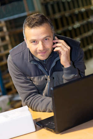 portrait of smiling storeman with laptop and using cellphone