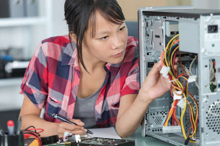 pretty young woman working with pc cables Imagens