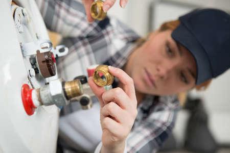 female technician lining up a threaded adapter Reklamní fotografie
