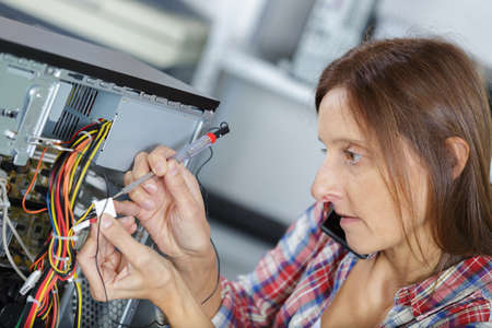 woman uses a screw driver to fix a pc