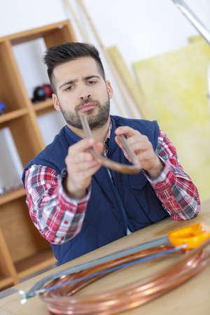 a man sawing transparent tube