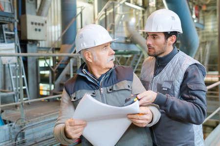 men in factory looking at paperwork Foto de archivo
