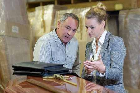 salesman and businesswoman discussing coffins