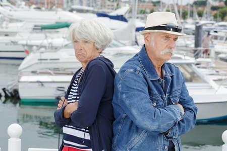 senior couple stood back to back after an argument