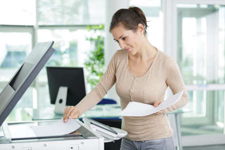 young secretary with papers standing by photocopier in office Stockfoto