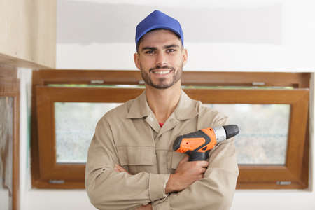 portrait of young tradesman holding a cordless drill