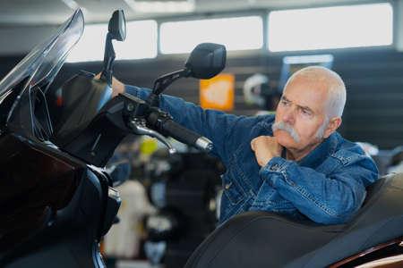 senior man trying motorbike at a salon