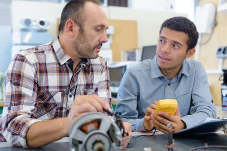 Apprentice and teacher in science workshop