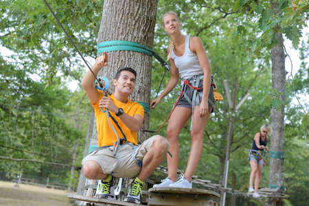 Instructor explaining adventure course through trees to adult woman
