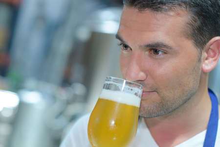 Close-up of brewer smelling beer at brewery Standard-Bild