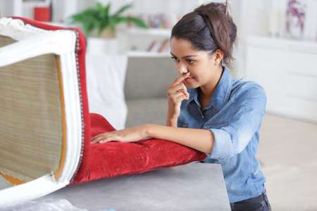 woman upholstering chair at home