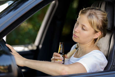 woman drinks beer while driving Foto de archivo