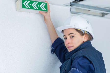 worker placing exit signs hanging at a wall Standard-Bild