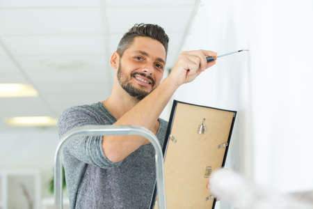 portrait of man hanging blank picture on wall Standard-Bild