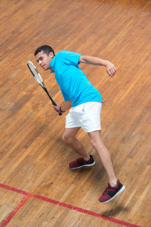young man lunging for ball during indoor tennis game