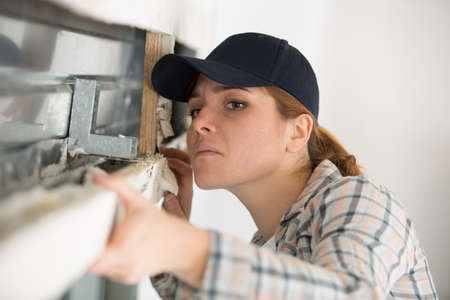 young female builder working with window