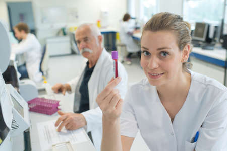 attractive female doctor showing a blood test