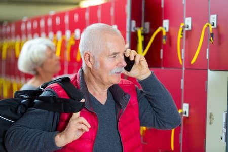 senior man using a phone in fitness club locker room 版權商用圖片