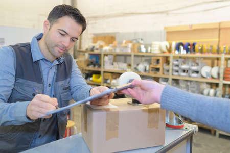 dispatcher of warehouse signing document before receiving goods Foto de archivo