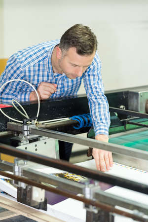engineer leaning over printing machine