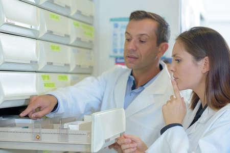 Pharmaists choosing medication from drawer