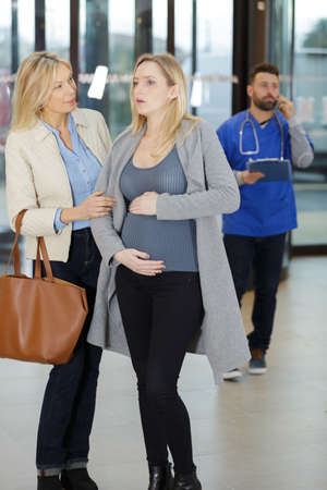 pregnant woman experiencing pain in hospital lobby