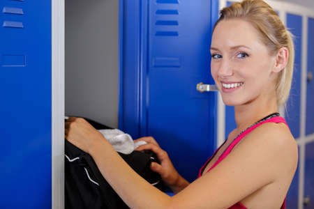 woman taking sports equipment from a locker Stock Photo