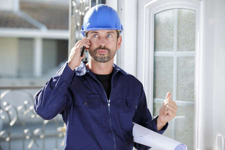 builder man is speaking to client on the phone