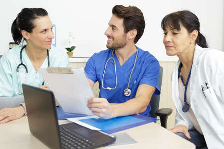 three medical staff sat around desk conferring