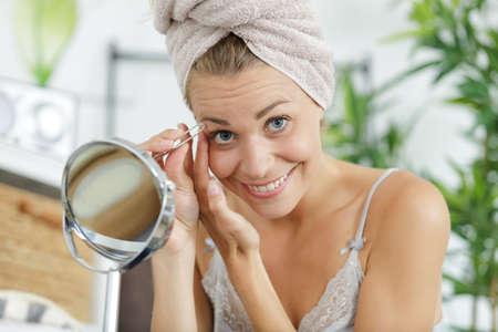a woman plucking eyebrows depilating