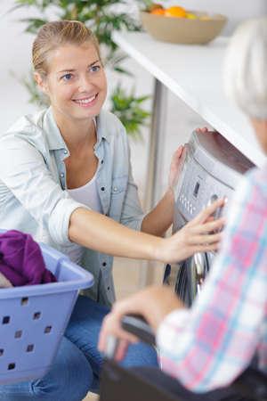 young woman helping senior to do a washing machine