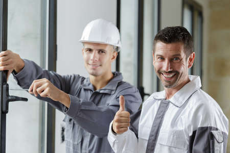 contractor fitting door handle with screwdriver supervisor holding thumbs up