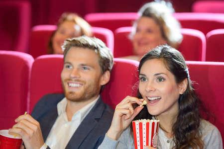 coppia felice che mangia popcorn mentre guarda un film al cinema