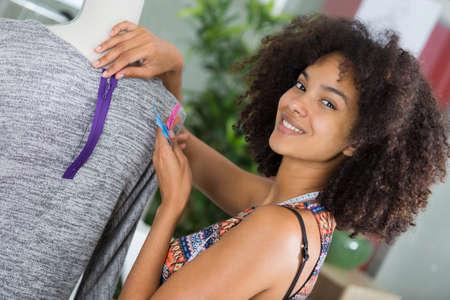 dressmaker matching zip to garment on mannequin