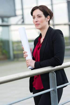 woman holding rolled blueprint