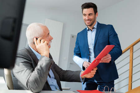 businessman passing file to ceo