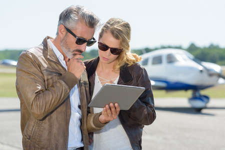 couple using a tablet next to a private jet 免版税图像