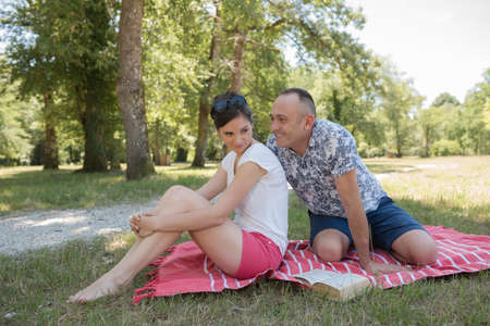 man tring to persuade sulking woman during picnic in park